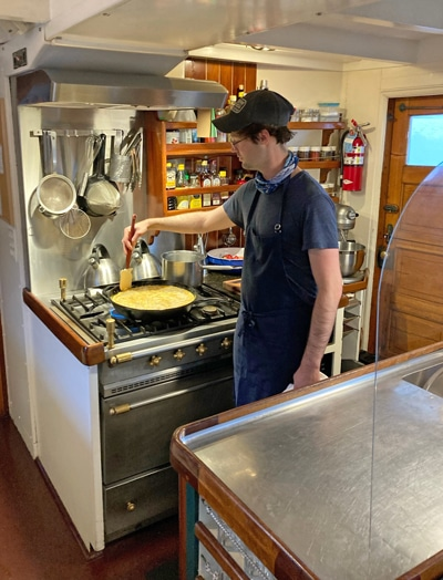 An open kitchen aboard Alaska small ship catalyst, the chef wears a blue apron and holds a spatula in a pan filled with food.