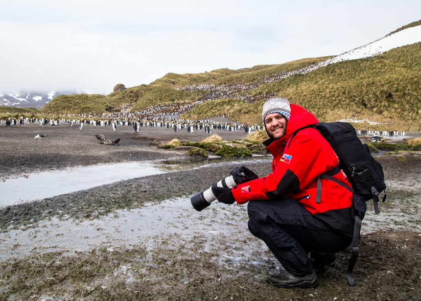 a man kneeling down and smiling as he takes photos of the large, scattered king penguin colony in antarctica