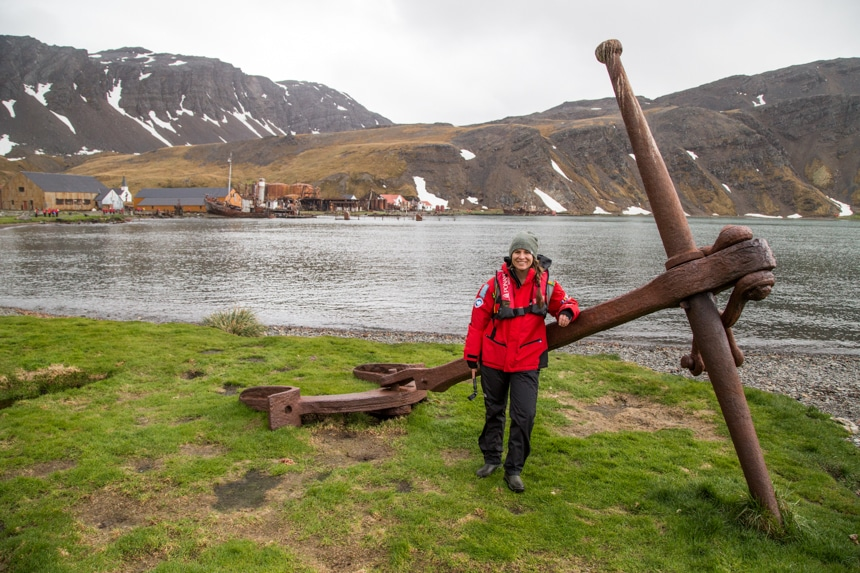 a woman standing in front of a large, rusted ship anchor that sits on the grassy shore in grytviken south georgia, antarctica