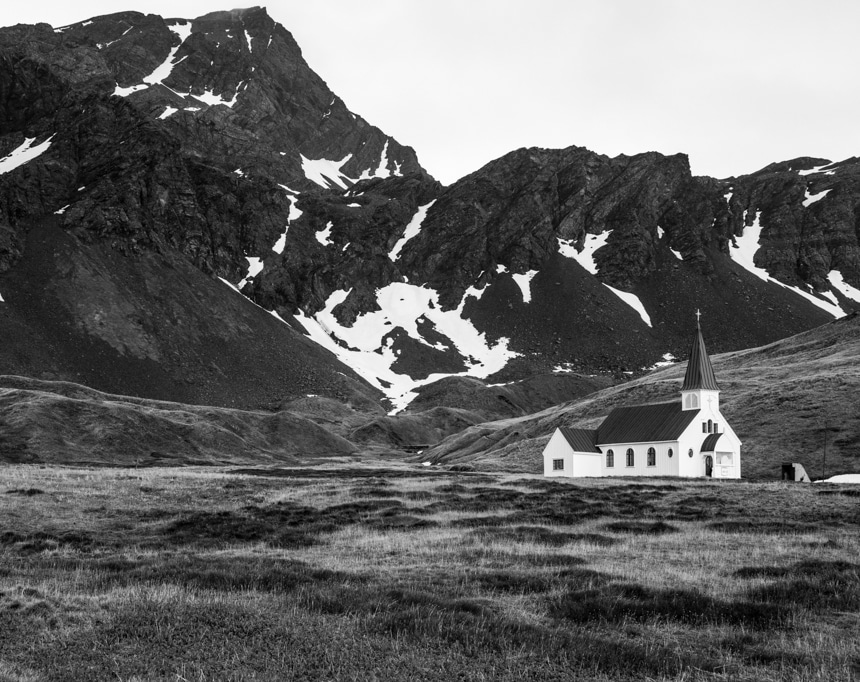 a black and white photo of church that sits among grassland below the tall mountains in grytviken, south georgia