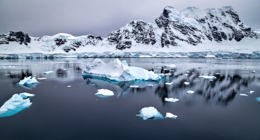 snowcapped icebergs floating in calm, grey ocean water in antarctica with snowcapped mountains in the background