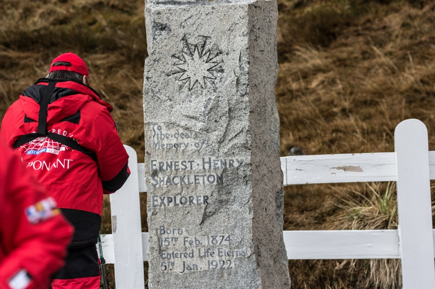 a person standing in front of shackelton's grave stone that stands in front of a white fence in grytviken, south georgia