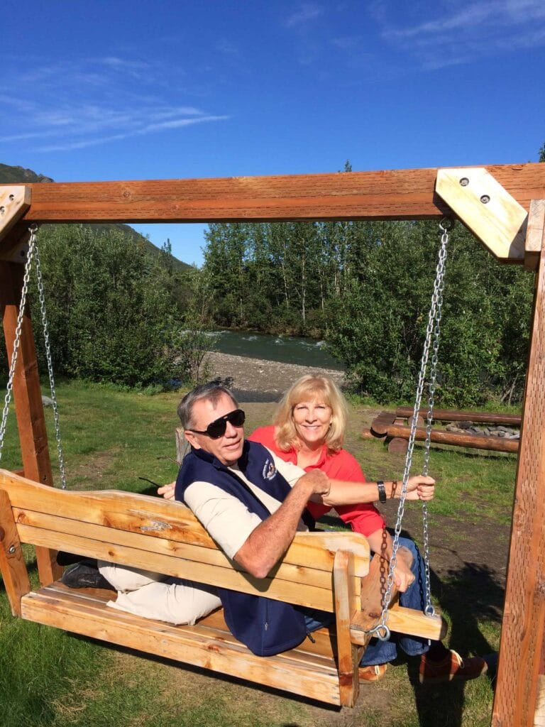 Happy traveling couple lounging on a swing next to a river in Alaska.