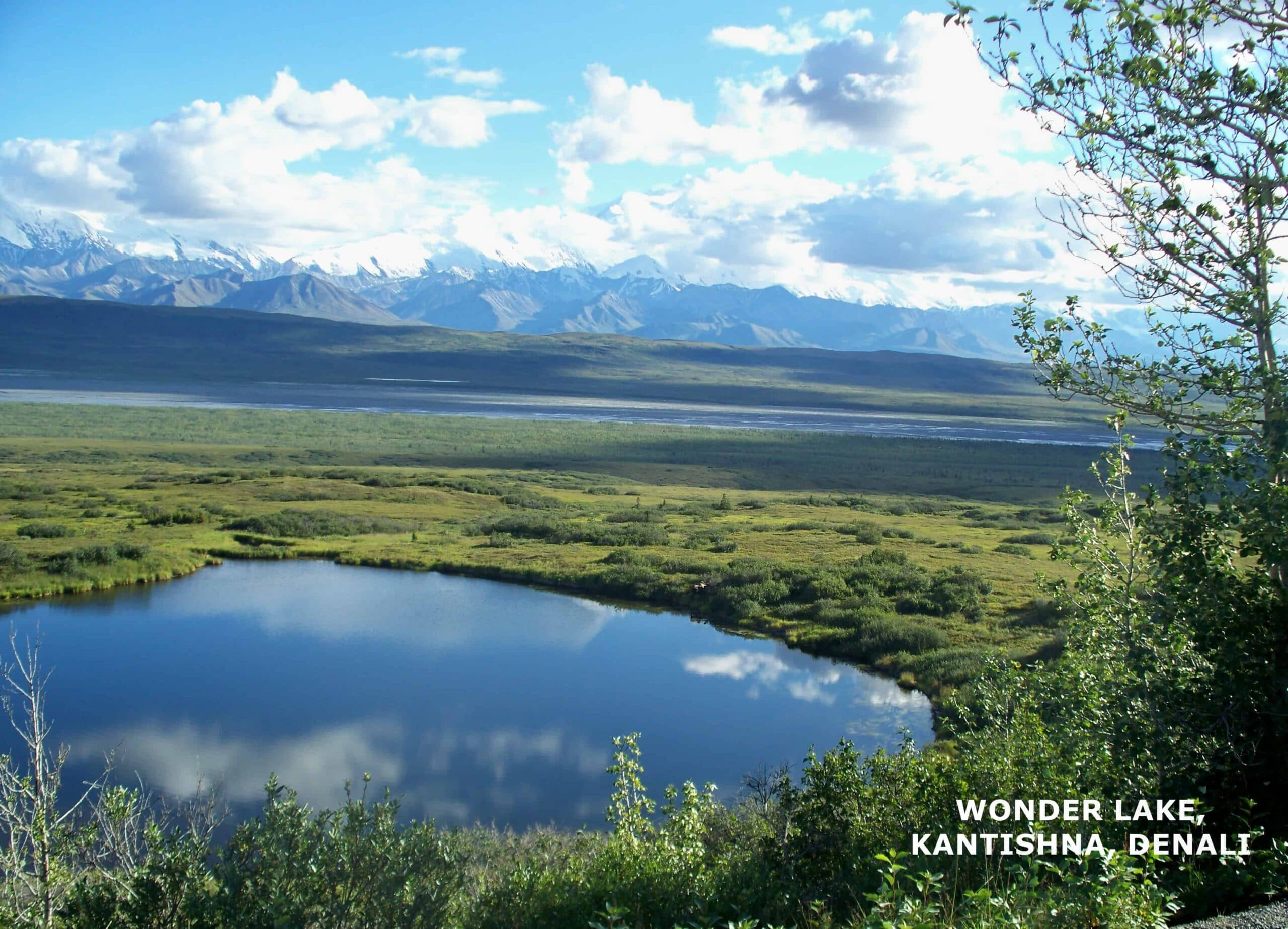 Wonder Lake surrounded by tundra with Alaskan mountain ranges.