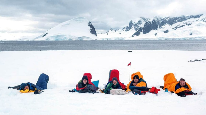 5 Antarctica cruise travelers participate in a camping activity in Antarctica, laying inside sleeping bags on sleeping pads on the snow.