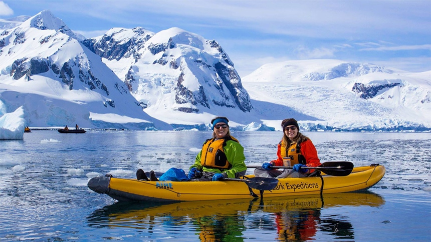 During a kayaking activity in Antarctica, two female travelers share a yellow double kayak and float in front of a snow covered jagged mountain range.