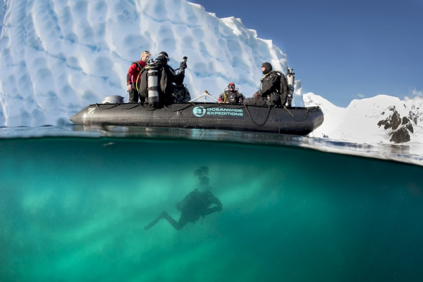 A party underwater image shows a polar diver In Antarctica swimming below a black inflatable skiff with other divers sitting aboard.
