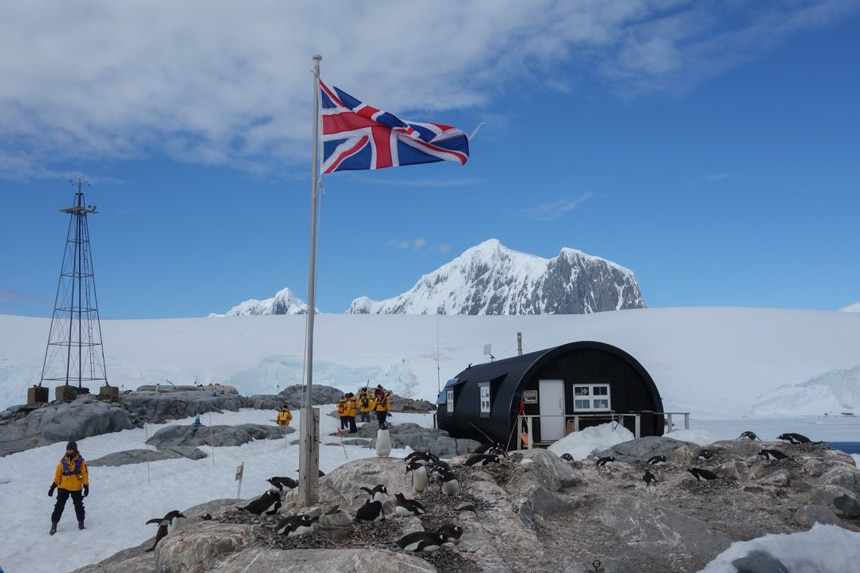 A flag pole with the British flag is front of Port Lockroy research station in Antarctica inside is a giftshop and post office where visitors can send letters and postcards.