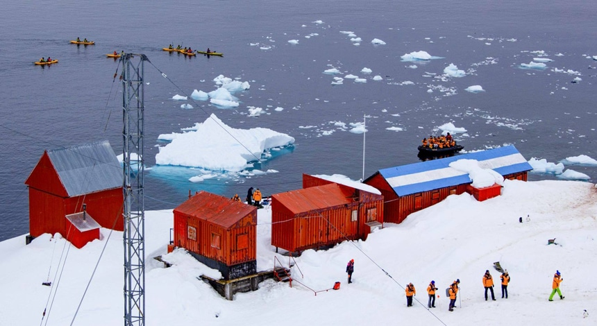 Brown Station research base sits on a snowy shore of Antarctica, travelers walk and kayak around its brightly red painted buildings.