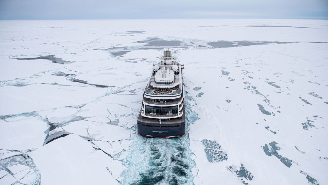 Aerial view of Le Commandant Charcot polar expedition ship cruising through ice during a Ross Sea expedition.