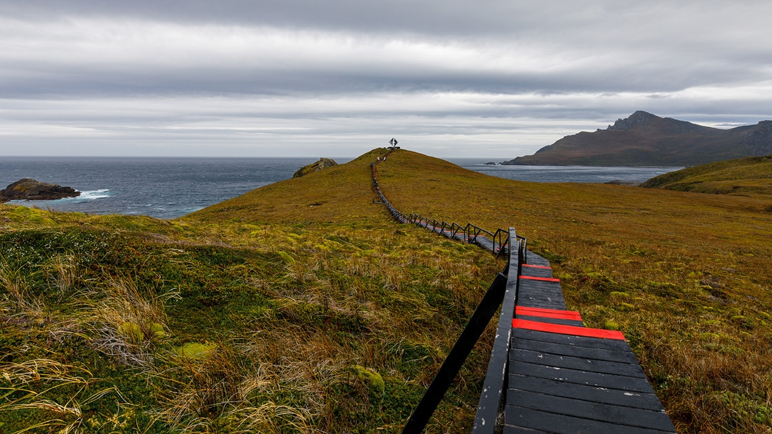 Wooden walkway painted black & red leads out to a silver statue at Cape Horn during the Essential Patagonia: Chilean Fjords & Torres del Paine Cruise.