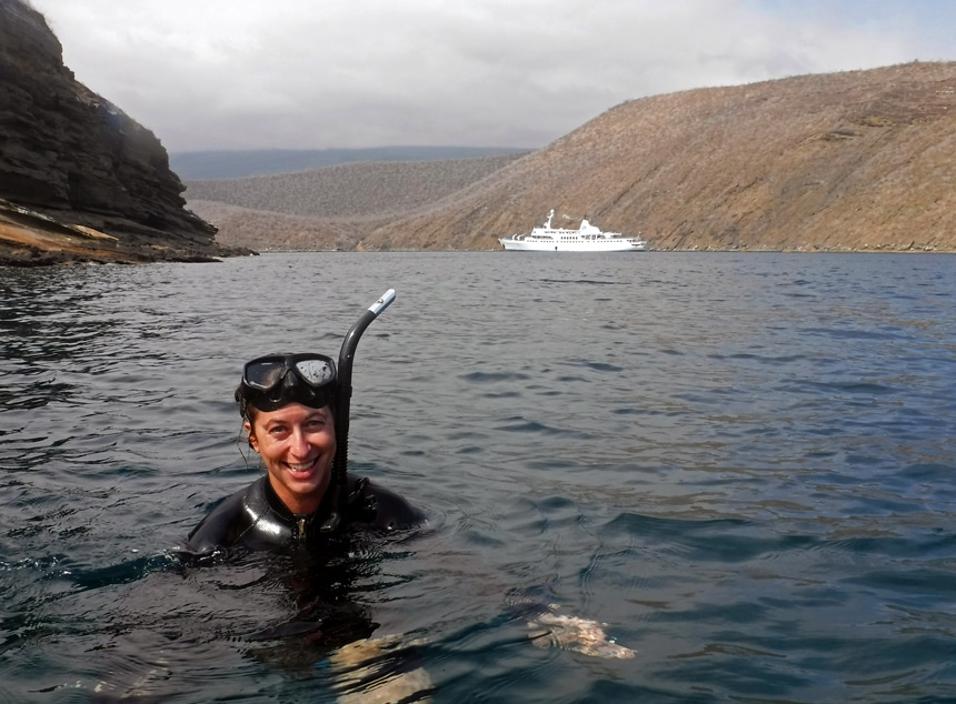 A female snorkeler floats at the surface of the dark ocean wearing a black wetsuit, mask and snorkel, behind her is a small Galapagos ship.