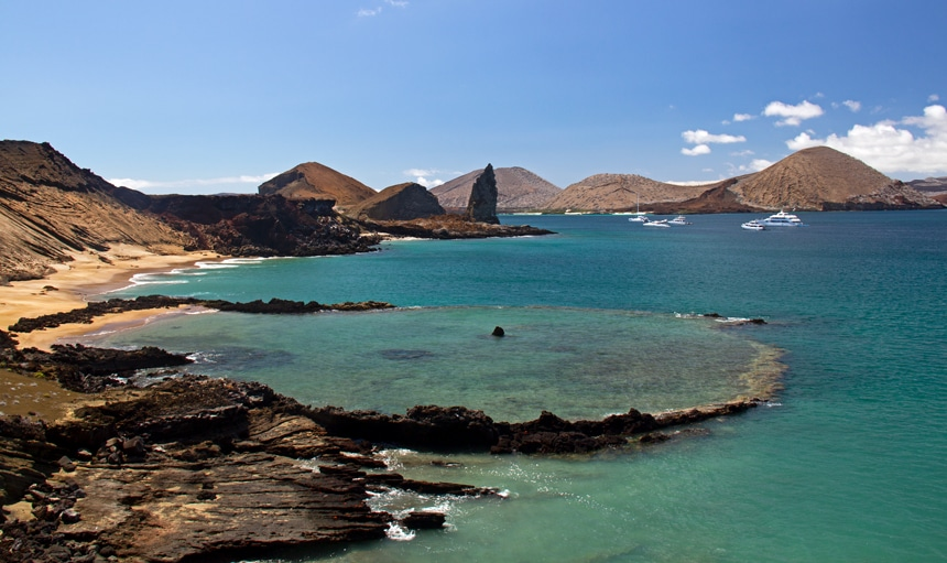 Blue sky and teal ocean water seen from Bartolome Island, black lava rock reach the ocean where a volcanic plug called Pinnacle Rock stands towards the sky.