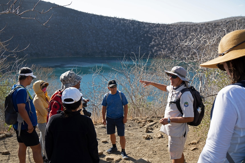 A Galapagos naturalist guide wears a tan uniform with wide brimmed hat speaks to his group and points to the landscape around them.