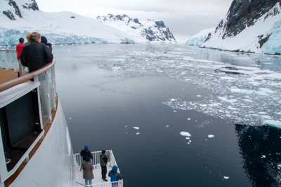 guests gather on the bow and observation wing to take in the view of floating icebergs and snowy mountain landscape of Antarctica,