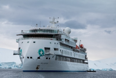 Exterior view of the modern Antarctic expedition ship Greg Mortimer, white and futuristic looking as it cruises the ocean.
