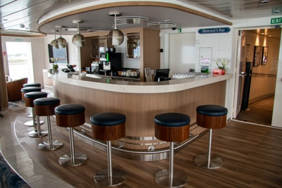 A set of bar height stools sit around the bar aboard Greg Mortimer Antarctic ship, circular light fixtured hang from the ceiling.