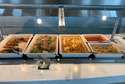 Food buffet selection aboard Greg Mortimer ship, white large serving plates set next to each other hold colorful menu items.