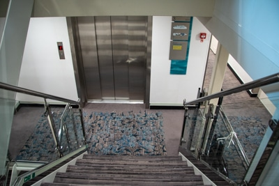 From the top of a set of stairs looking down at the metal doors of the Greg Mortimer's on board elevator.