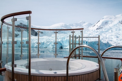 A jacuzzi surrounded half way with glass sits on the top deck with views of the snowy Antarctica landscape the ship cruises by.