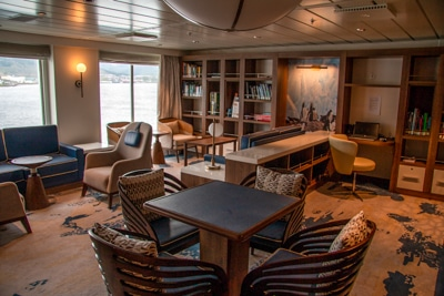 Library and lounge aboard Greg Mortimer ship, computer desks, artwork, shelves filled with books accent chairs and seating areas.