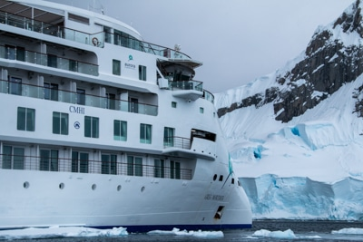 The front exterior of modern Greg Mortimer ship, futuristic and white with decks of windows and wrap around walkways.