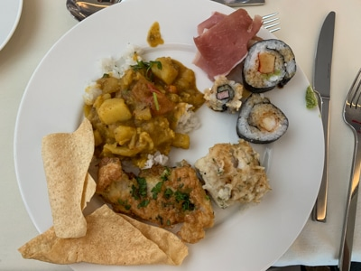 Dinner plate filled with a selection of sushi, curry with rice and other menu items served aboard Greg Mortimer ship.