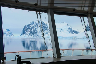Looking out through glass windows from the observation deck towards a jagged snow covered mountain range in Antarctica