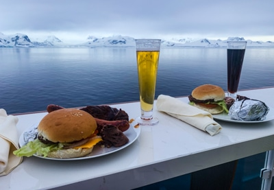Dinner with a view. Plated food and tall drink glasses are set on an outdoor table facing the ocean towards snow capped mountains of Antarctica
