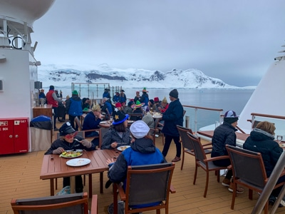 On the top deck of Greg Mortimer ship, guests enjoy their meal outside at tables with views of Antarctica's snowy mountain ranges.