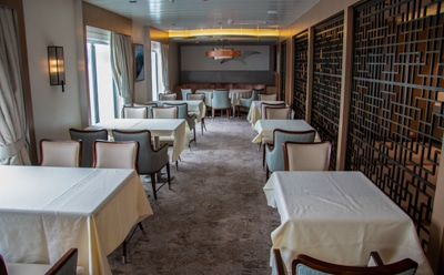 The empty dining room aboard Greg Mortimer Antarctic Ship, tables covered with table cloths and upholstered accent chairs set in rows.