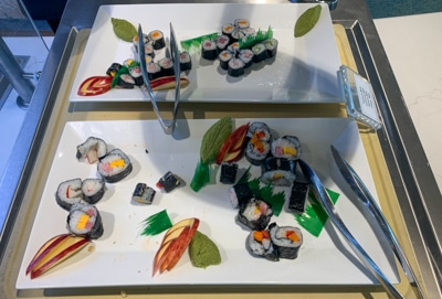 Two white serving plates filled with colorful sushi rolls and metals tongs, part of buffet dinner aboard Greg Mortimer ship.