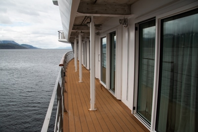 The wrap around outside walkway on the deck aboard Greg Mortimer luxury Antarctica ship, wooden floor with handrails infront of glass cabin doors.