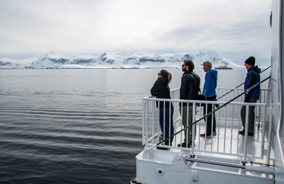 A group stand on the lowered hydraulic platform that extends from the side of the Greg Mortimer ship and look out over the Antarctic landscape.