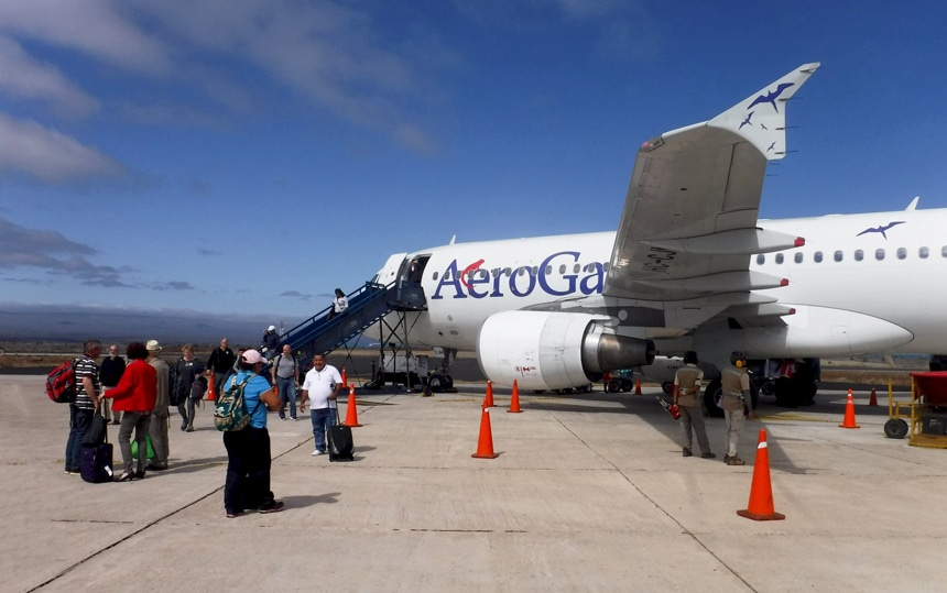 Outside on the airport runway stand Galapagos travelers with their luggage waiting to board a white airplane labeled Aero Galapagos.