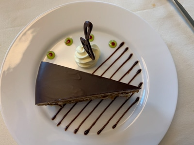 Slice of deletant chocolate cake on a white plate decorated with lines of chocolate served for dessert aboard Greg Mortimer ship.