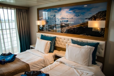 Stateroom aboard Greg Mortimer ship, two double beds, sliding glass balcony doors, and a large Antarctica landscape framed photo overhead.