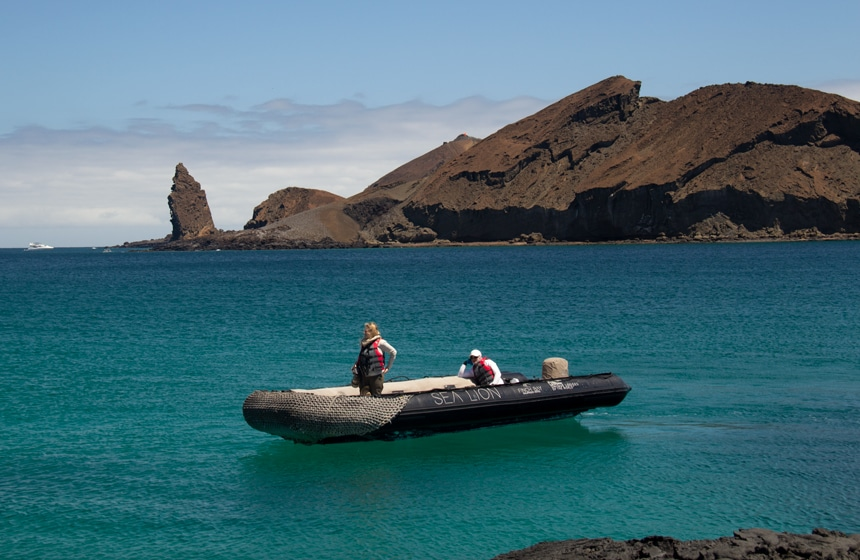 Pinnacle Rock, a volcanic plug on Bartolome Island, rises from the teal ocean as a black inflatable skiff cruises around in front of it.