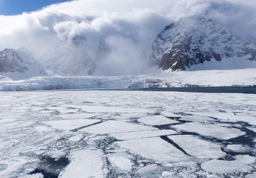 An ice field in the waters of the Arctic Svalbard. The ice fit like puzzle pieces as they float in front of a massive ice shelf and snowy mountain range.