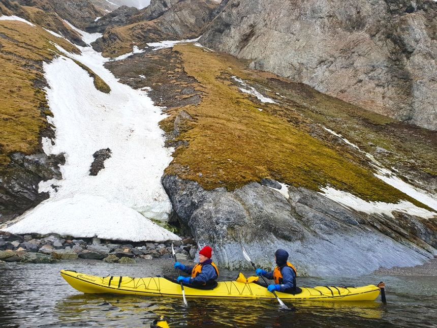 Against the shore line of an Arctic island in Svalbard two guests wearing winter gear paddle a yellow double kayak through the ocean.