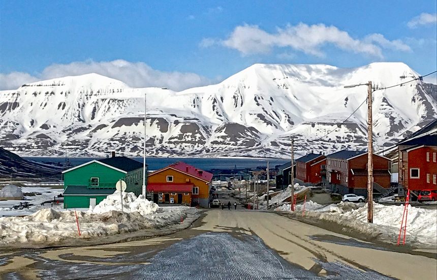 The town of Longyearbyen on Spitsbergen Island has brightly colored buildings sit in front of a massive snowy mountain range.