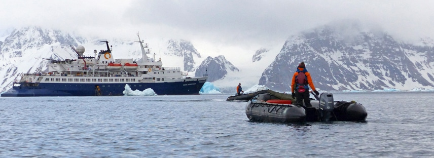 A guide drives an inflatable skiff through the water towards the ocean adventurer expedition ship floating among ice bergs in the Arctic.