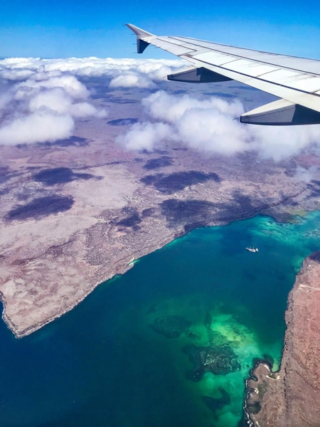 Photo from the Galapagos airplane window, looking over the airplane wing down at and the crystal teal blue ocean water surrounding the islands below.