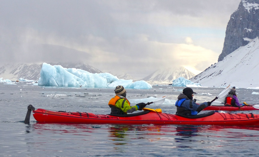 Arctic cruise guests in jackets and beanies paddle red double kayaks through the icy ice berg filled waters of Svalbard.