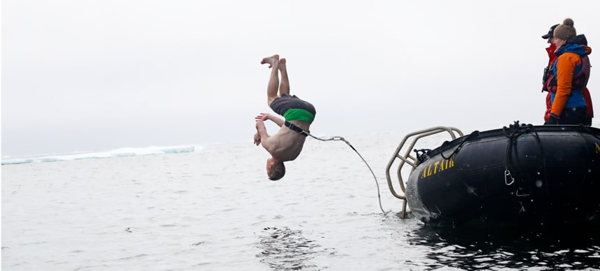 Polar plunge! A man flips into the arctic ocean in front of an ice shelf. He is harnessed to a black inflatable skiff for safety.
