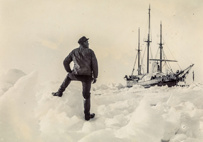 A vintage 1893 photo of famous explorer Nansen stands on shore with one foot on an ice berg staring at the Fram expedition ship stuck among thick icebergs.