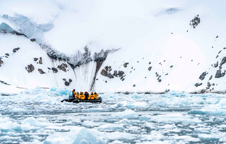 A black inflatable skiff filled with passengers in yellow parkas navigate the ice berg filled waters of the Arctic against a snowy shoreline.
