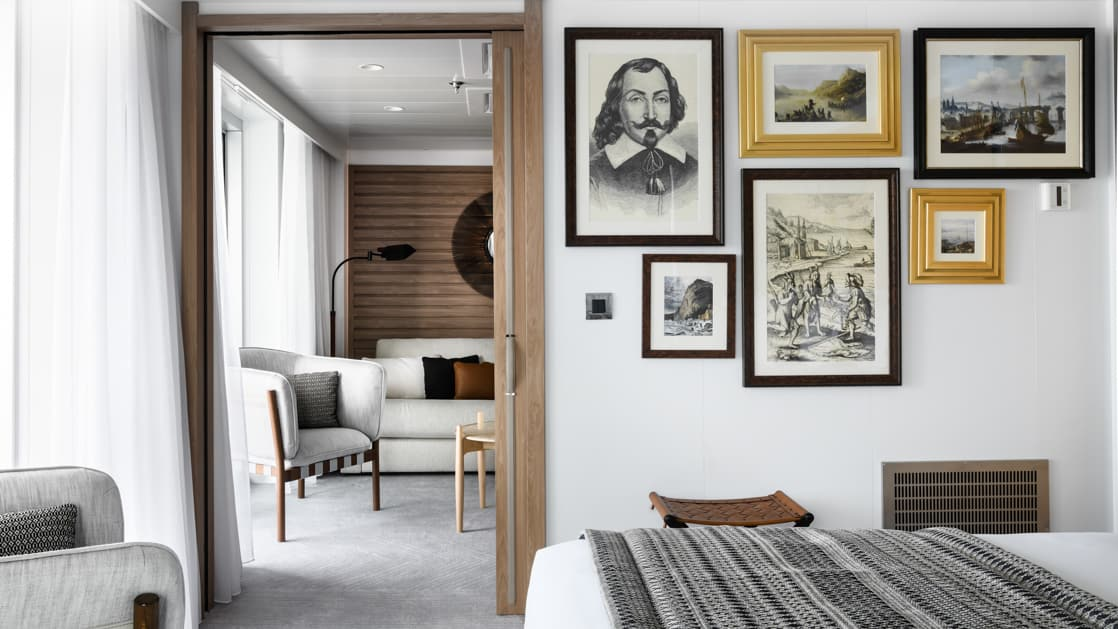 Owner's Suite aboard Le Dumont D'Urville luxury expedition ship, showing king bed, separate living room, bright white decor & photos & drawings of explorers on the walls.