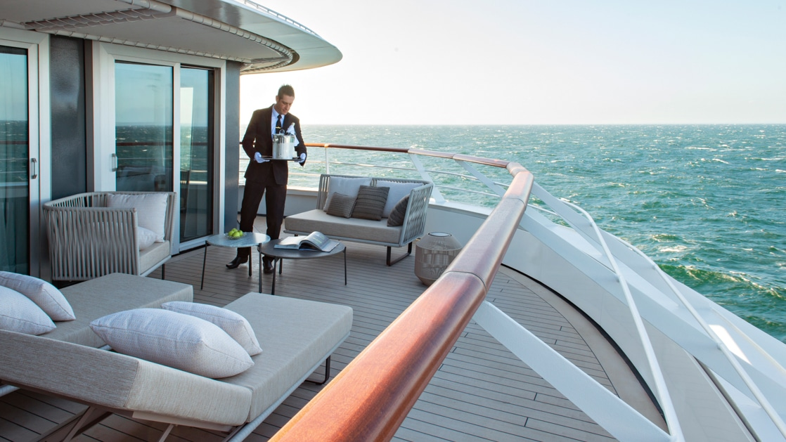 Server in formal wear & white gloves delivers a chilled bottle of champagne to an empty deluxe suite terrace of Le Jacques Cartier French ship as she sails in open waters.