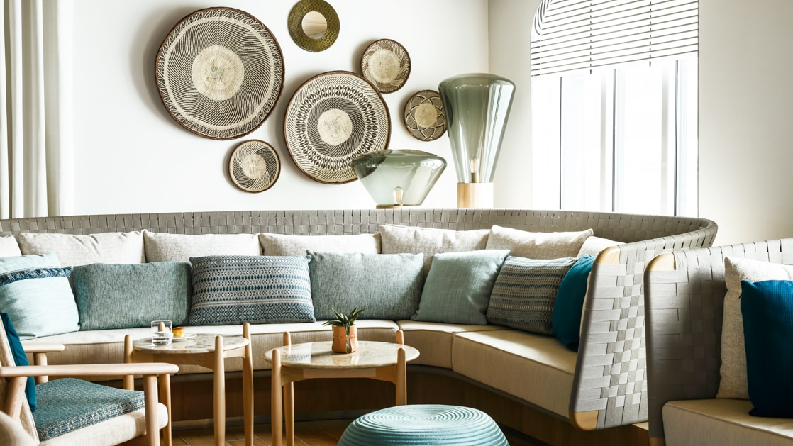 Wraparound couches with woven gray backs & many pillows bask in sunlight under woven bowls affixed to the wall above, on Le Jacques Cartier luxury ship.